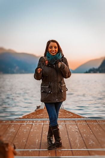 Portrait of woman standing on pier against lake during sunset