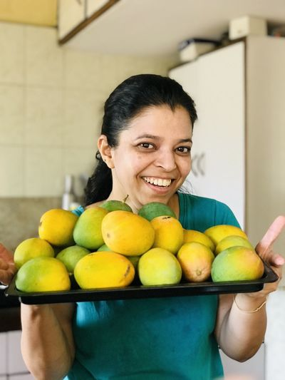 Portrait of smiling woman holding fruits
