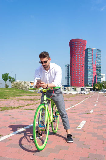 Man riding bicycle on street against clear blue sky