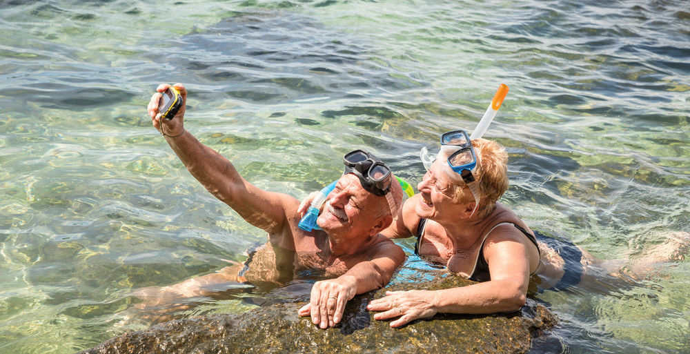 Senior couple taking selfie in sea