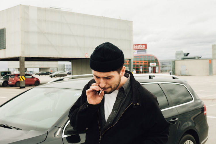 Young man using mobile phone in car