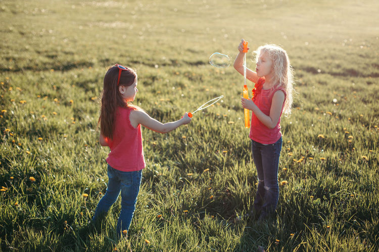 Girls playing with bubble wand