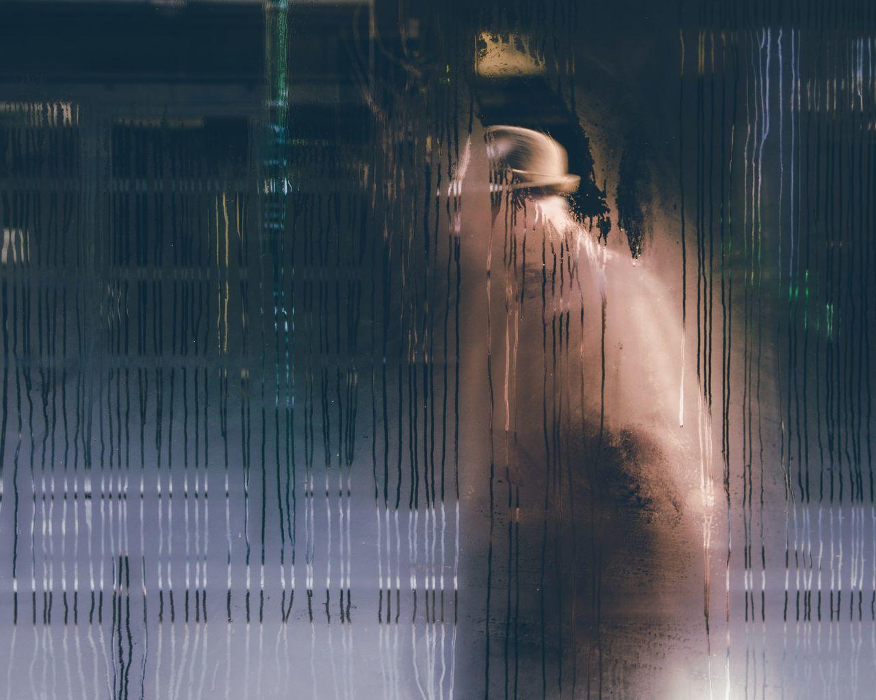 Person seen through wet window