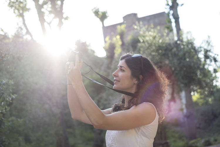 Side view of woman photographing with camera during sunny day