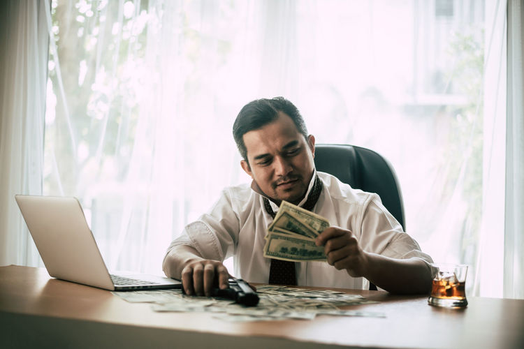 Smiling Mid Adult Businessman Holding Money And Gun While Sitting In Office