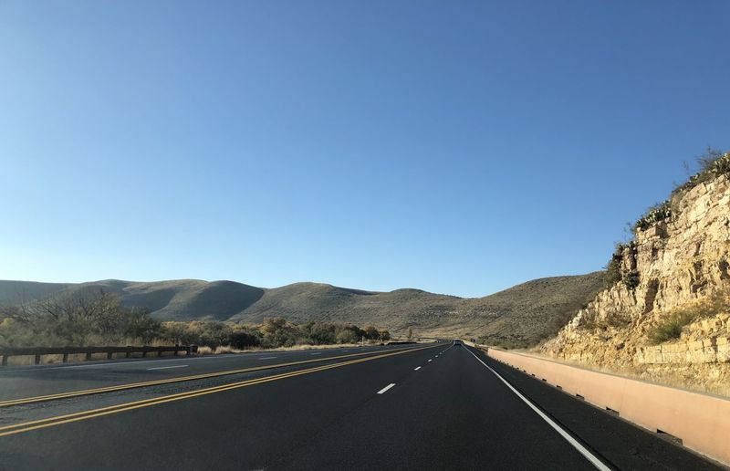Empty highway road in New Mexico. New Mexico Landscape The Way Forward Two Lane Highway Highway Empty Road No People Copy Space Clear Sky Sunny Diminishing Perspective Mountain Range Dividing Line Blue Outdoors Mountain Remote Location Absence Ranch USA Road Trip Transportation Country Road Hills And Valleys Desert Landscape