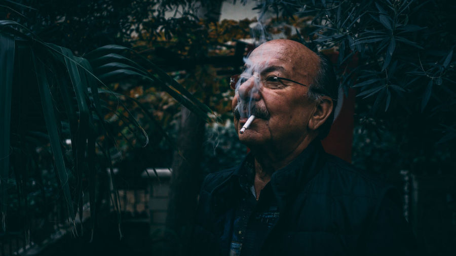 Man smoking cigarette against trees