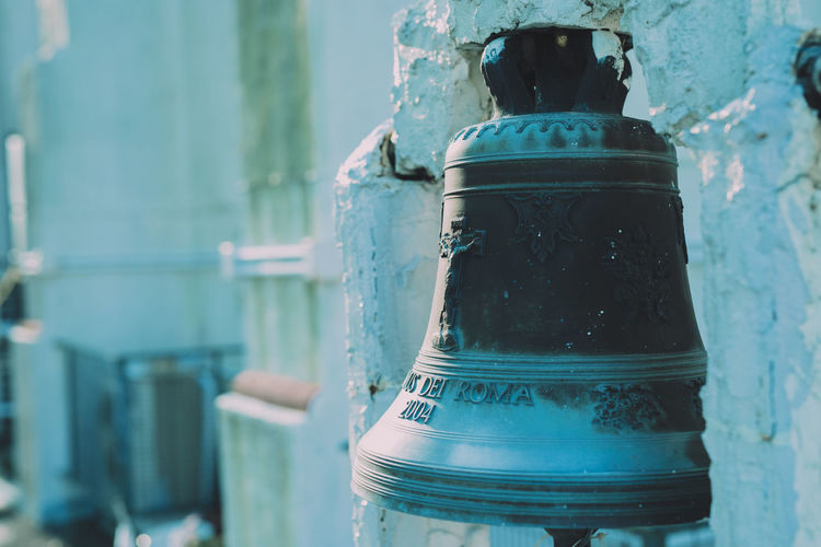 Close-up of bell hanging at church during winter