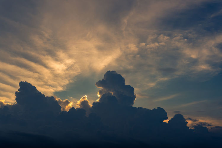 Low angle view of sunlight streaming through clouds during sunset