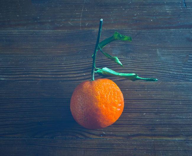 tangerine on wooden table Orange Green Brown Daylight Soft Light Still Life Structure Texture Surface Peel Fruit Vitamin Healthy Quiet Mandarin Wood Wooden Woody