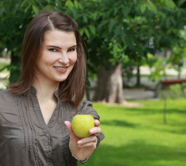 Smilling young woman offering a green apple outside in a park Portrait Smiling Looking At Camera Young Adult One Person Happiness Holding Brown Hair Front View Focus On Foreground Green Color Beautiful Woman Offering Apple Apple - Fruit Green Apple Books Food Healthy Eating Diet Nutrition Young Woman Smiling Woman Portrait