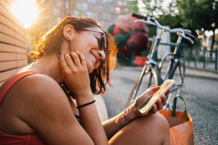 Young woman using mobile phone while sitting in city