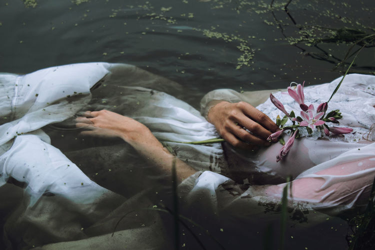 Midsection of woman with flower drowning in lake