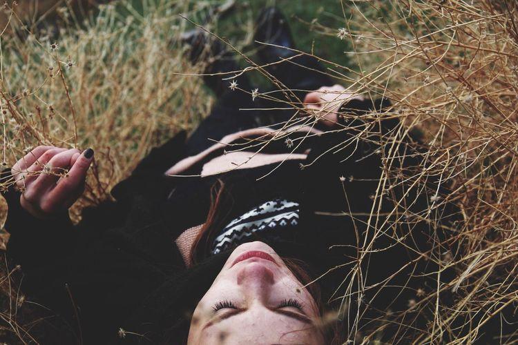 Woman lying down on dry plants
