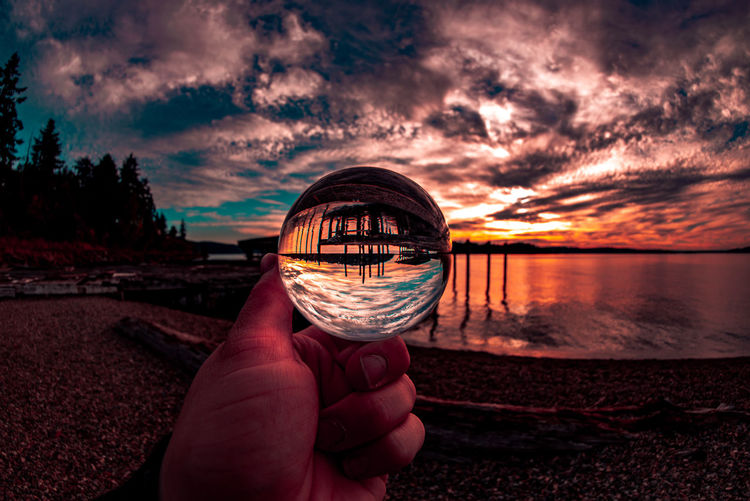 Midsection of person holding crystal ball on beach against sky during sunset