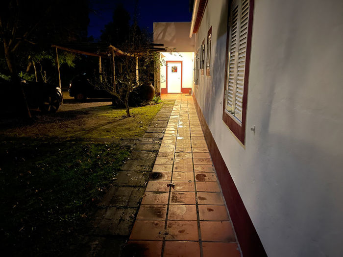 Footpath amidst buildings in city at night