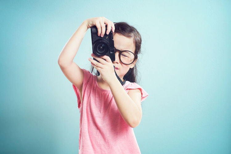 Girl photographing through camera while standing against blue background