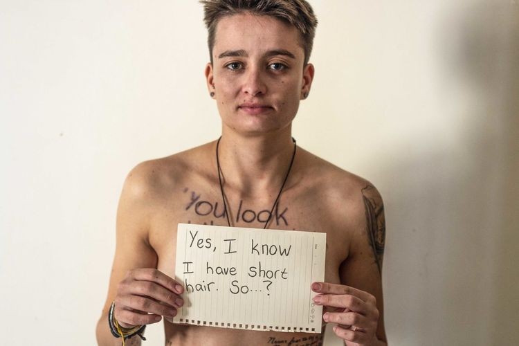 Portrait of shirtless young woman showing paper with text against wall