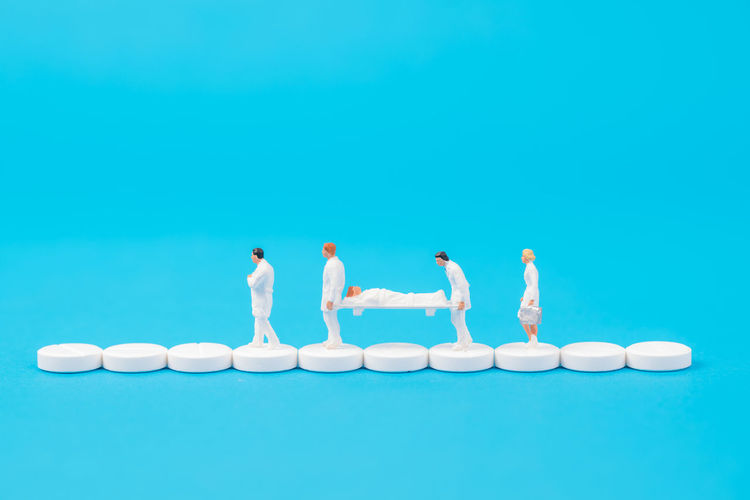miniature people healthy team and medical drug,medical concept Doctor  Drug Hospital Medicine PainKiller Teamwork Therapy Antibiotic Blue Blue Background Figurine  Healthcare And Medicine Miniature People Patient Pill Small Treat