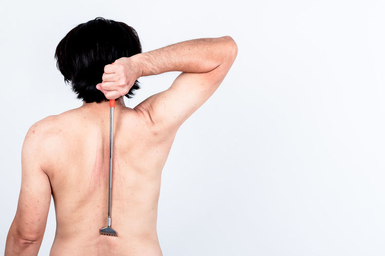 Rear view of shirtless woman standing against white background