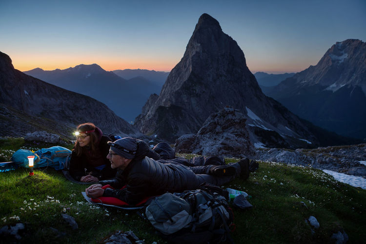 Hiking couple relaxing on mountain at sunset