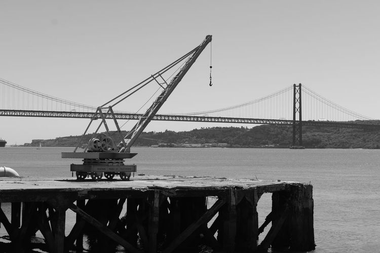 Suspension bridge over river against clear sky