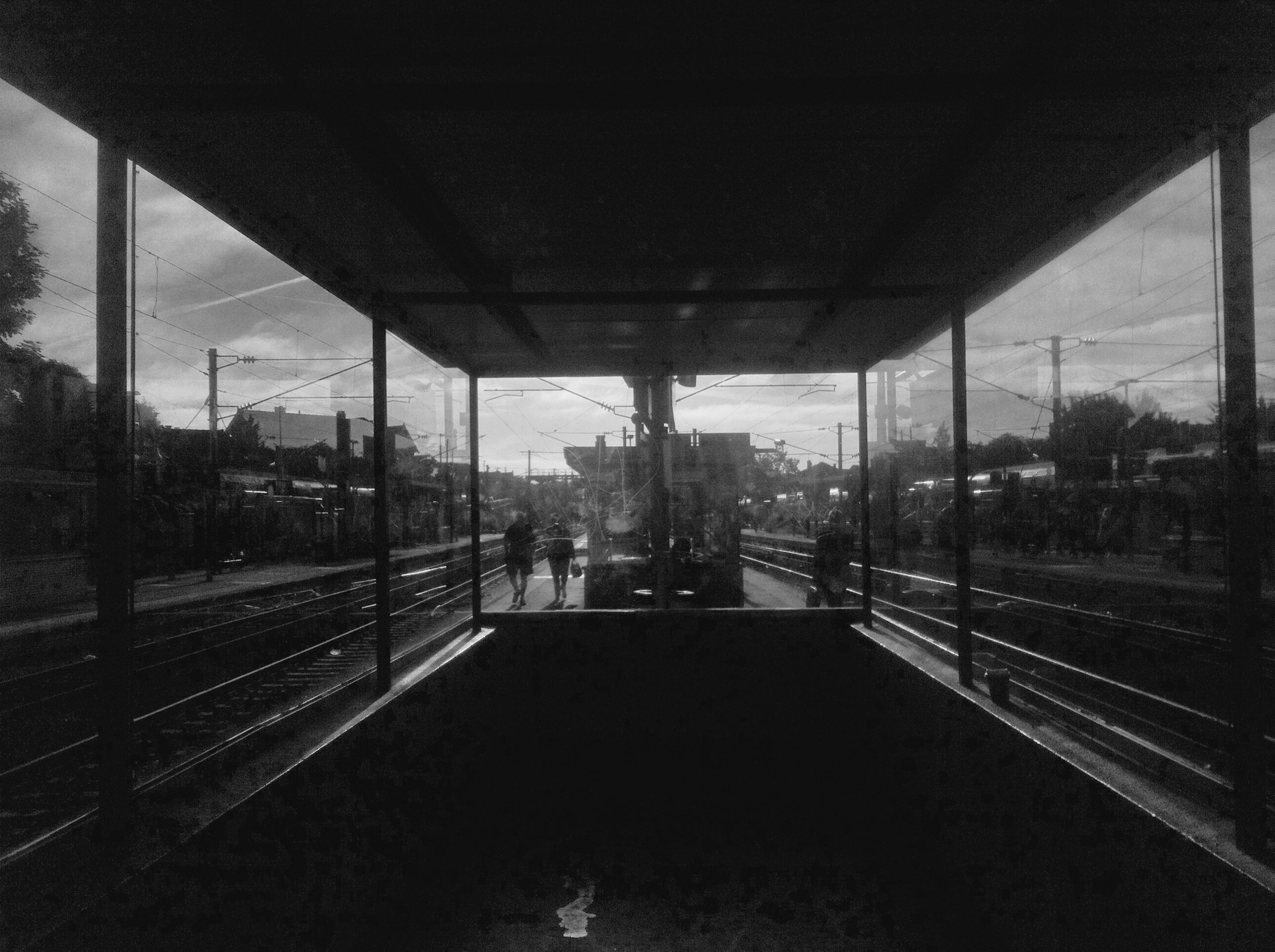 transportation, railroad track, the way forward, architecture, built structure, public transportation, rail transportation, railroad station platform, diminishing perspective, tree, mode of transport, railroad station, city, sky, incidental people, indoors, travel, city life, vanishing point