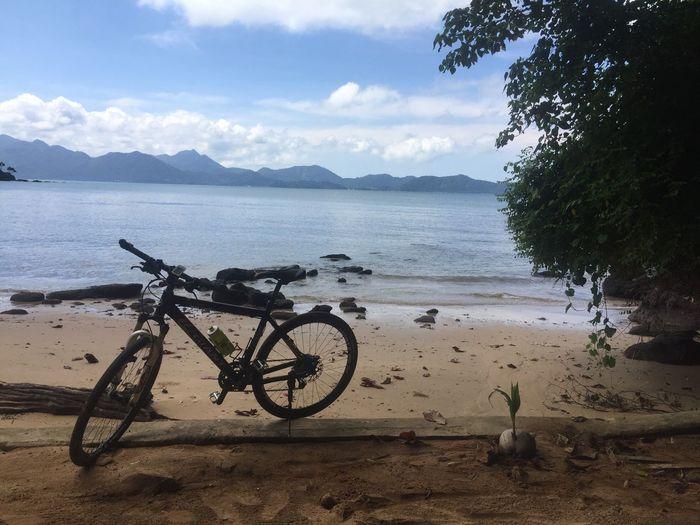 Bicycle on beach against sky