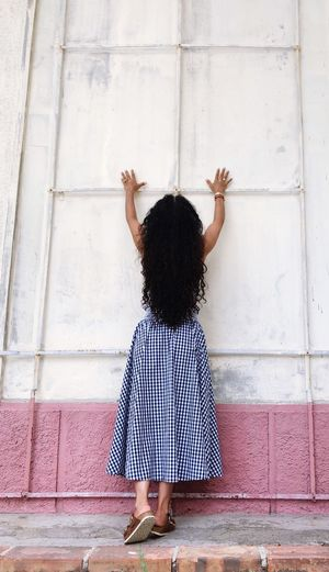 Rear view of woman with arms raised standing against wall