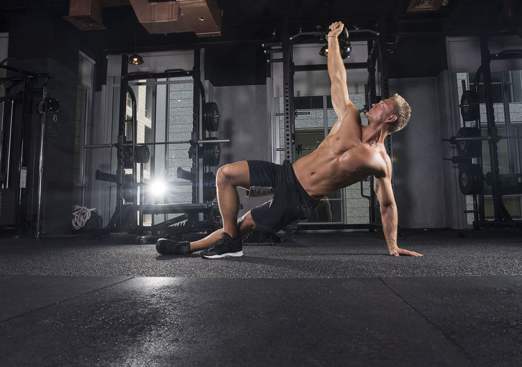 Young Man Exercising With Kettlebell At Gym