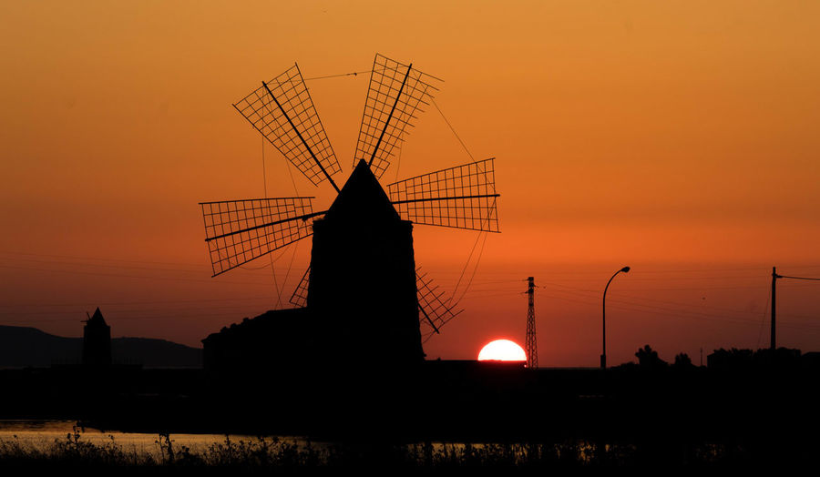 Silhouette traditional windmill against orange sky