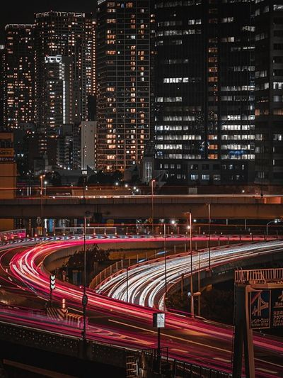 Light trails on road against illuminated buildings in city