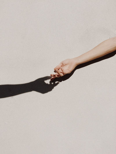 Midsection of woman holding hands against white background