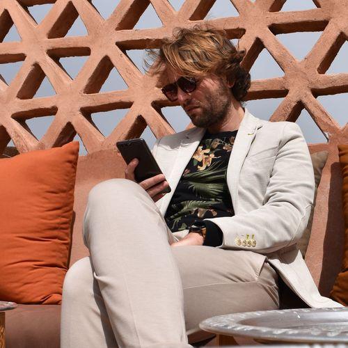 Man Using Phone On Sofa