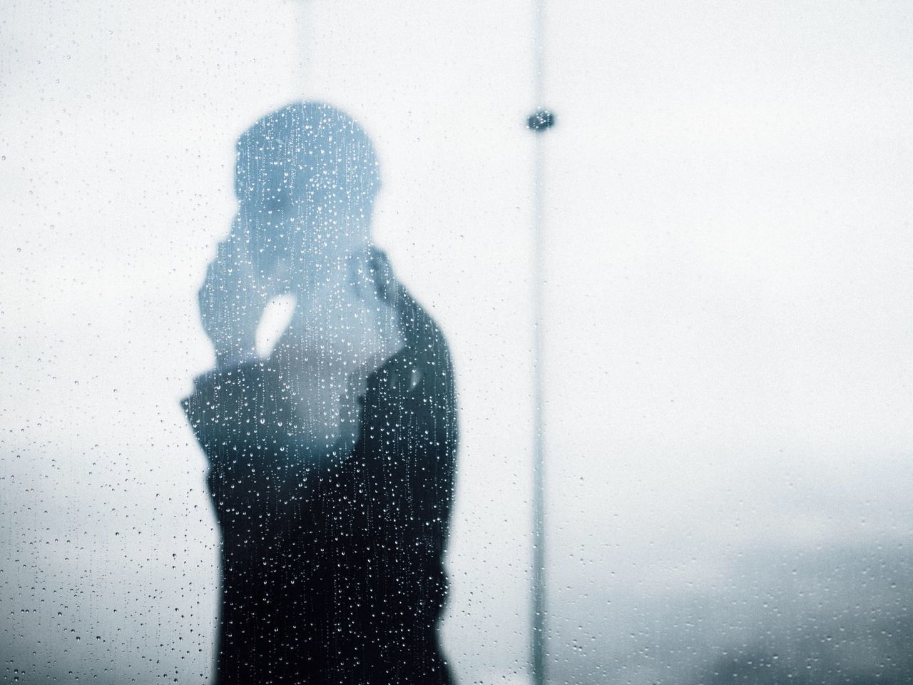Side view of a silhouette man against waterdrops on glass
