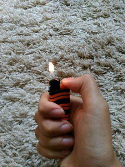 Cropped hand holding lighter over carpet