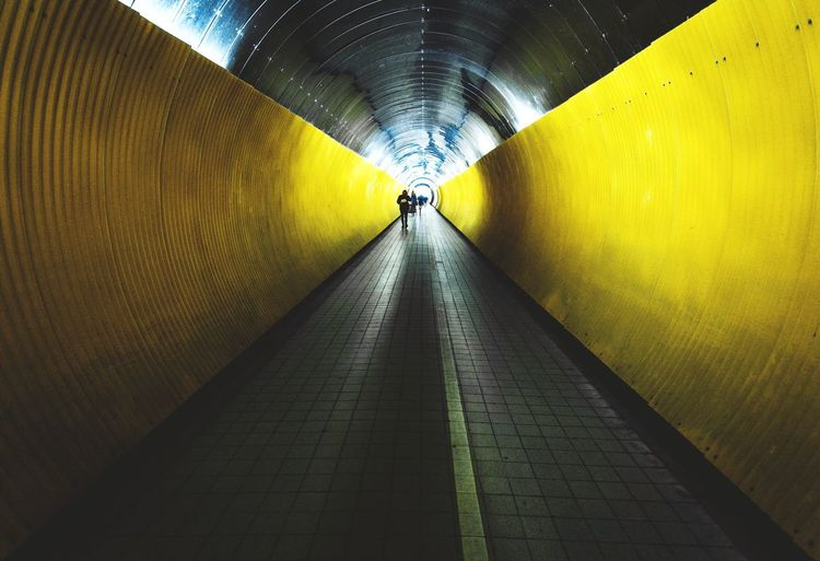 Person walking in illuminated tunnel
