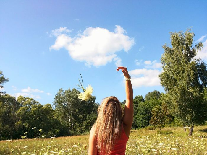 Young woman with arms raised against trees