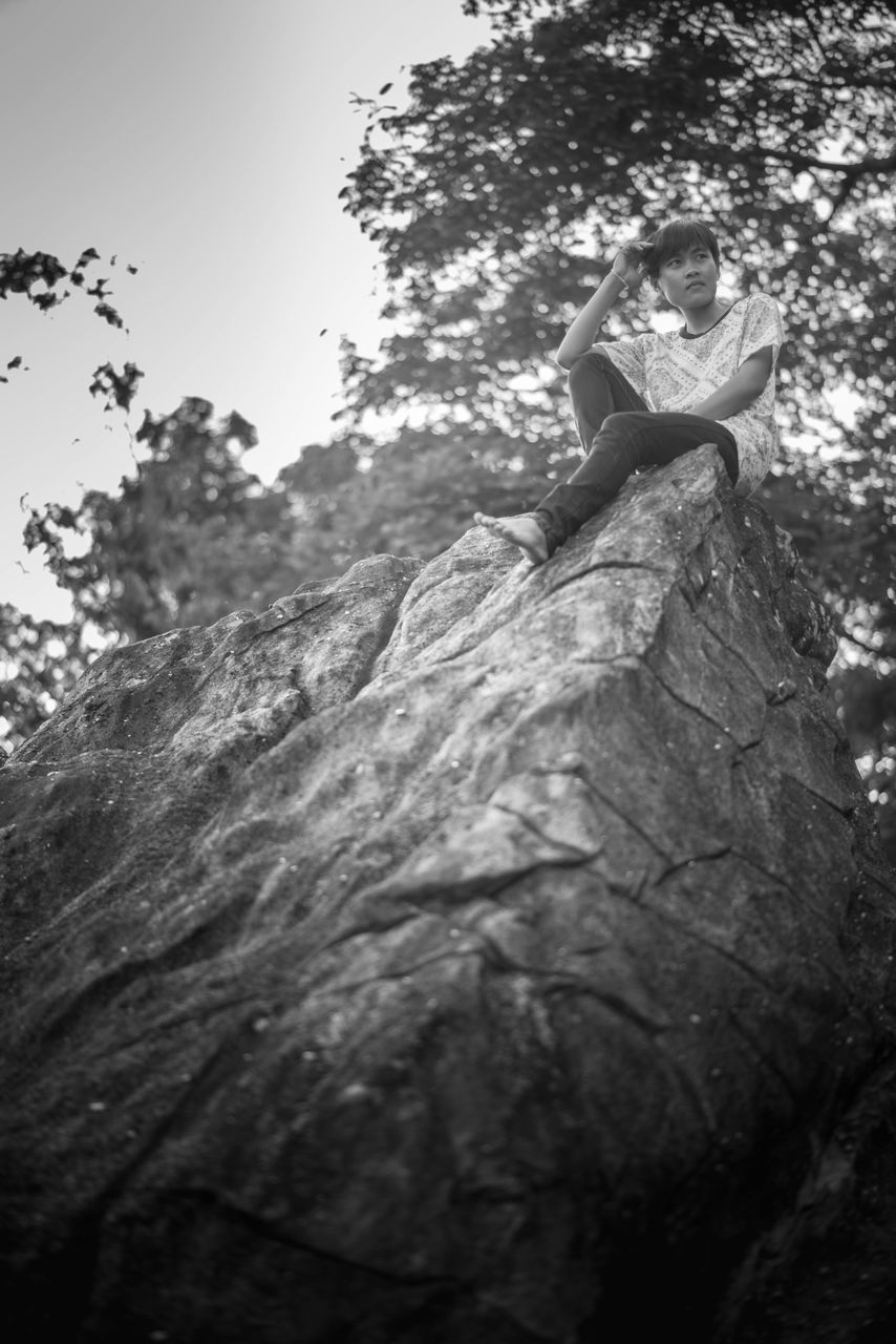 Low Angle View Of Teenage Boy Sitting On Rock By Trees In Forest