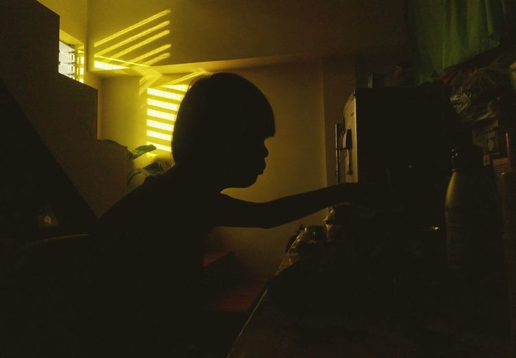 Side view of silhouette boy sitting at home