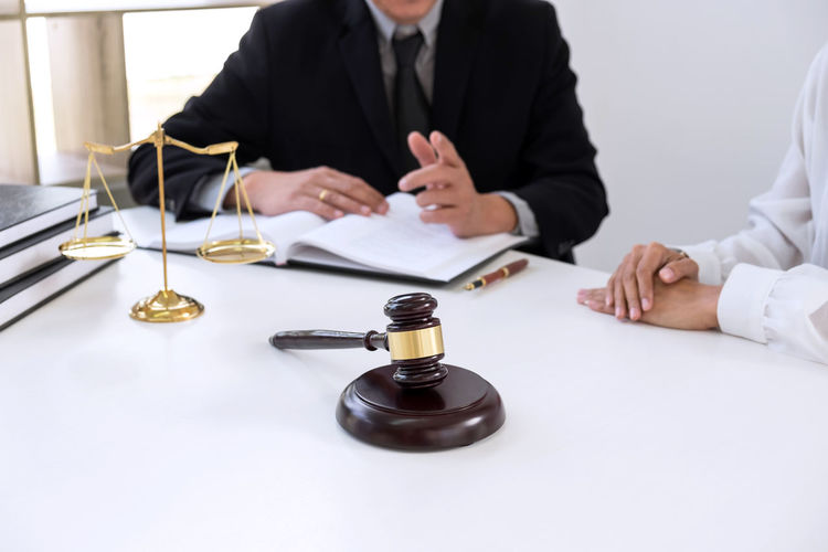 Midsection Of Lawyer Discussing With Client On Desk