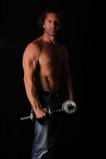 Portrait of shirtless bodybuilder man standing against black background