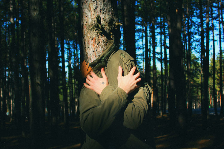 Man covered with coat in forest
