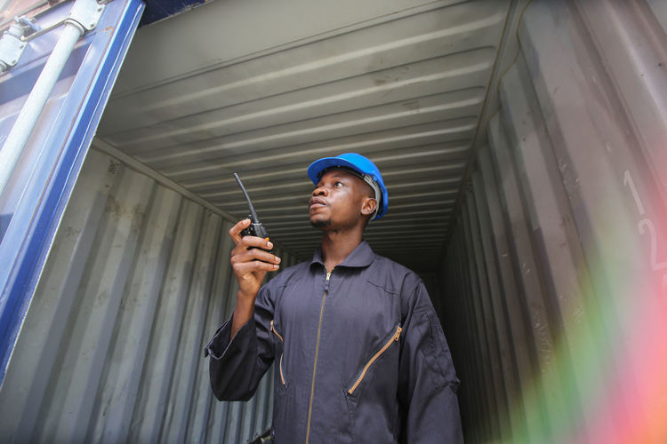 Worker taking on walkie-talkie while standing under cargo container