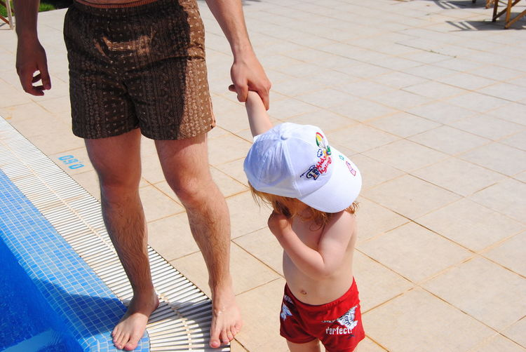 Low Section Of Father With Son Standing At Poolside