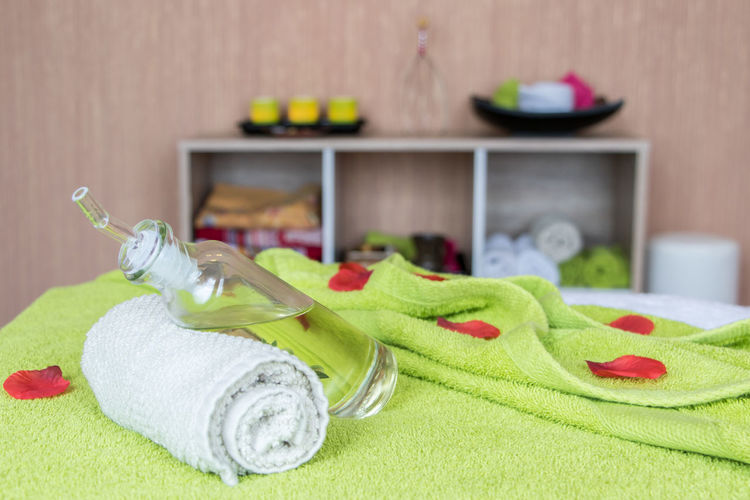 Close-Up Of Spray Bottle With Towel On Bed