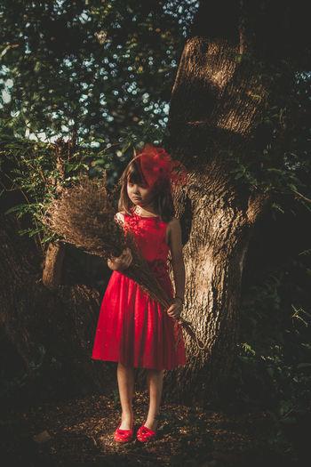 Full length of girl standing by tree trunk