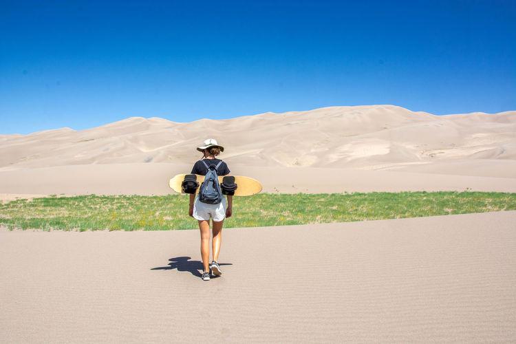 Full length rear view of woman walking with sandboard in desert