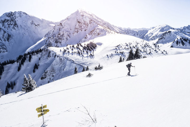 Mature man skiing on snow covered mountain against sky during sunny day