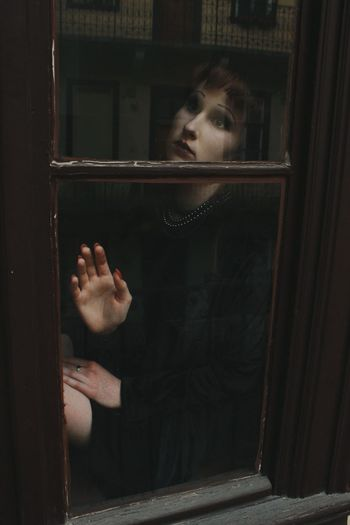 Portrait of a doll looking through window